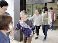 職員の介助を受けて避難所に向かう訓練に参加した施設入所者=北海道南富良野町の「一味園」で2017年8月24日午後1時31分、安達恒太郎撮影