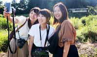旧蛸島駅近くに置かれたままの車両(右奥)を背景に記念写真を撮る埼玉県出身の3人組=石川県珠洲市で、石川将来撮影