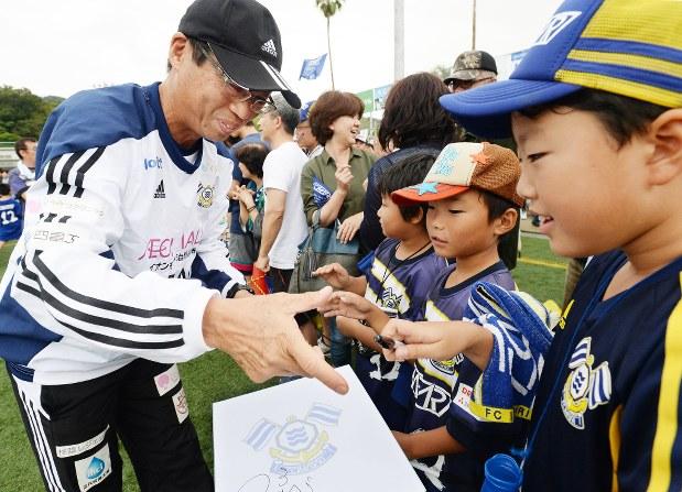 子供たちからサインを求められる岡田武史・FC今治代表(左)=2016年9月25日、加古信志撮影