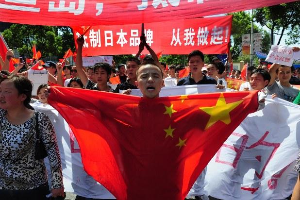 中国国旗を掲げ、日本の尖閣諸島国有化に抗議する反日デモの参加者=2012年9月16日、隅俊之撮影