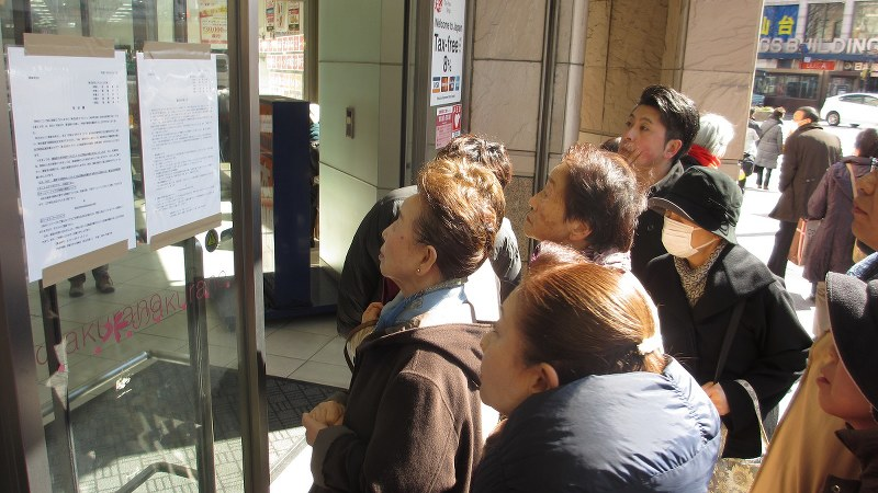 さくら野百貨店仙台店入り口で営業停止を知らせる張り紙を見る買い物客ら=2017年2月27日、鈴木一也撮影