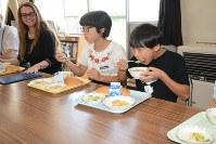 ブラジェンカ・フラスティッチさん(左)とクロアチア料理を食べる児童ら=十日町市南鐙坂の鐙島小で