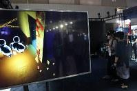 左側の画面に映っているホラー空間を探索中の体験者2人(右側)=東京ゲームショウで
