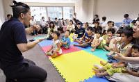 集いの場「こめっこ」の一場面。手話を使って絵本を読み聞かせる男性スタッフ(左)の動きを子供たちが楽しそうに見つめていた=大阪市中央区で、花澤茂人撮影