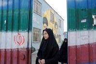 イラン国旗が描かれた高校の正門を出るレイラ・ハサンプールさん(手前)。校舎の壁には最高指導者ハメネイ師(左)と故ホメイニ師の肖像が描かれている=イラン北東部マシャドで1月