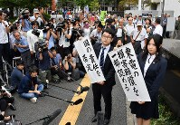 Lawyers for the plaintiffs in a lawsuit seeking damages from the government and TEPCO for residents who evacuated to Chiba Prefecture following the 2011 Fukushima nuclear disaster hold up banners reading