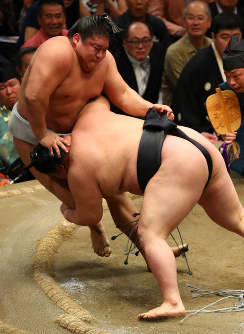 Ozeki Goeido, right, tackles maegashira Takanoiwa on Day 14 of the September Grand Sumo Tournament at Tokyo's Ryogoku Kokugikan sumo venue, on Sept. 23, 2017. Goeido leads the tourney with a record of 11-3, with yokozuna Harumafuji at 10-4. (Mainichi)