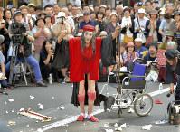 パフォーマンスを終え、声援に応える大道芸人のギリヤーク尼ケ崎さん。紙に包まれた「投げ銭」が路上に散らばる=札幌市中央区で2017年8月27日、竹内幹撮影