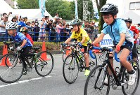 沿道の声援を受けながら、自転車を力強くこぎ進める児童ら=前橋市大手町で