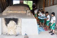 ペーパーウエートを登り窯から取り出す生徒たち=島根県大田市の大田市立第三中学校で、関谷徳撮影