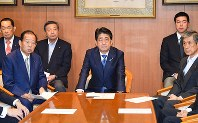 Prime Minister Shinzo Abe, center, is pictured at a special meeting of the Liberal Democratic Party (LDP) Board on Sept. 25, 2017. Sitting on the left is LDP Secretary-General Toshihiro Nikai, and on the far right is party Vice President Masahiko Komura. (Mainichi)