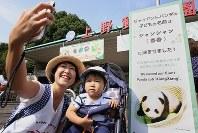 上野動物園の正門前に置かれた看板の前で記念撮影をする親子連れ=東京都台東区で2017年9月26日午前10時1分、宮武祐希撮影