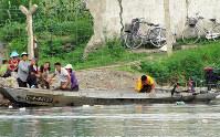 鴨緑江で漁をする人たち。背後の鉄条網は脱北防止のためにある=朝中国境で2017年7月末、石丸次郎さん撮影