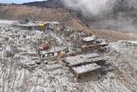 山頂(中央上)に建っていた御嶽神社の奥宮は既に解体され、御岳頂上山荘の建物(右)の解体も進んでいる=長野県木曽町で2017年9月25日午後2時21分、本社ヘリから手塚耕一郎撮影