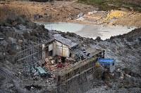 御嶽山の山頂直下に建つ御嶽頂上山荘では、重機を使って建物の解体が進められていた。奥は二ノ池=長野県木曽町で2017年9月25日午後2時44分、本社ヘリから手塚耕一郎撮影