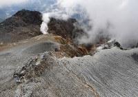 左下は多くの犠牲者が生じた御嶽山の山頂。南側斜面(上)では、今も噴煙が立ちのぼっている=長野県木曽町で2017年9月25日午後2時23分、本社ヘリから手塚耕一郎撮影