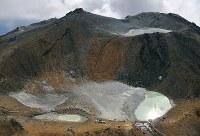 噴火から3年を迎えた御嶽山。中央奥は、多くの犠牲者が生じた頂上の剣ケ峰。二ノ池(手前右)の近くには、別の小さな池(手前左)ができている=長野・岐阜の両県境付近で2017年9月25日午後2時24分、本社ヘリから手塚耕一郎撮影