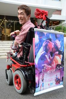 映画「パーフェクト・レボリューション」主人公のモデルになった熊篠慶彦さん。車椅子の後ろに映画のポスターをつけてアピール=中嶋真希撮影