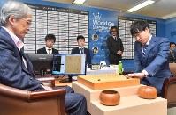 本因坊文裕(右)と対局する「DeepZenGo」。左端はZenを操作する加藤英樹さん=大阪市北区で3月23日、森園道子撮影