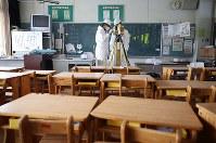 大熊町立大野小学校の教室を3D撮影する測量士ら=福島県大熊町で22日、宮武祐希撮影