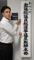 選挙違反取締本部の看板を掛ける捜査員=滋賀県警本部で、森野俊撮影