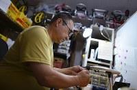 車椅子を製作する川西英治さん=大阪市住之江区で2017年8月25日、久保玲撮影