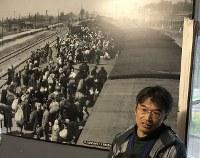 説明する中谷剛さん。写真は、ビルケナウに停車した列車から降り立つ人々。1車両あたり約70人がトランクとともに詰め込まれ、数百キロ以上も離れたところから、運ばれた=ポーランド・オシフィエンチムで2017年9月17日午後3時8分、鈴木美穂撮影