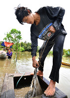 川底に掘った穴から金鉱石などを採掘するコンプレッサーマイニングの現場で働くウィンシー・リャーミスさん=フィリピン・カマリネスノルテ州ホセパガニバンで、川平愛撮影