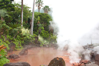 Steam billows up from a rust red hot spring near the