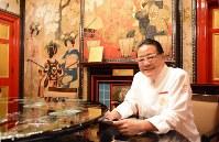 中国料理「旬遊紀」の「玉城の間」で近藤紳二シェフ。手前の第1号の回転テーブルや壁面には一面に装飾が施されている