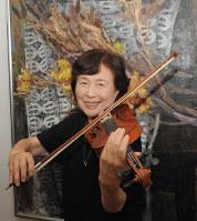 自宅玄関に飾られた父の油絵「栗(くり)と白レース」の前でバイオリンを弾く寺井秋代さん
