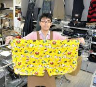 10Lサイズの下着を広げるライオン堂4代目店主の久保田純平さん