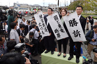 Lawyers hold a banner saying