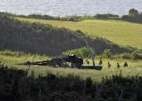 牧草地に不時着後、炎上した米軍の輸送ヘリコプターCH53E=沖縄県東村高江で2017年10月12日午前7時40分、徳野仁子撮影
