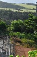 牧草地に不時着後、炎上した米軍の輸送ヘリコプターCH53E(奥)=沖縄県東村高江で2017年10月12日午前7時40分、徳野仁子撮影