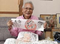 自身の手による絵手紙を広げる小池邦夫さん。「誰にもできることを誰にも出来ない程やりつづける」は妻の恭子さんに宛てた=東京都狛江市で2017年10月4日、宮本明登撮影