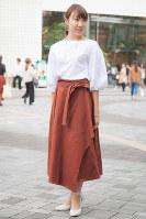 ボリューム袖のトップスにベルテッドのボトムスを合わせた女性=日本ファッション協会提供