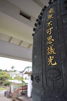 西・元死刑囚の名が刻まれている「生命の鐘」。奥は納骨堂=鹿児島県鹿屋市の星塚敬愛園で
