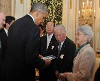 拉致被害者家族会の(右から)横田滋・早紀江夫妻、飯塚繁雄代表と面談し、めぐみさんの写真を見つめるバラク・オバマ米大統領=東京・元赤坂の迎賓館で2014年4月24日(内閣広報室提供)