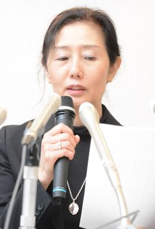 Plaintiff Ryoko Tsuya is seen holding the written verdict in Akita on Oct. 16, 2017. (Mainichi)