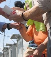 仮設住宅で候補者(左)と握手する候補者=熊本県西原村で、津村豊和撮影(画像の一部を加工しています)