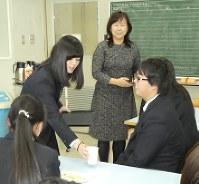元キャビンアテンダントの槙田あずみさん(左から3人目)の前で、英語で飲み物サービスをする夕張高校の生徒たち=夕張市の同校で