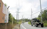 米軍ヘリの事故があった沖縄県東村高江の集落を通る米軍車両。近くに米軍北部訓練場が広がる=沖縄県東村高江で2017年10月16日
