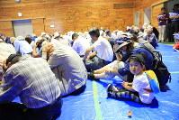 ミサイル発射を想定した訓練で、頭を押さえる住民=北海道滝川市で9月1日、梅村直承撮影