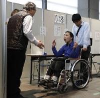 ヘルパーの代筆による期日前投票ができるよう投票所の担当者と交渉する中田泰博さん(中央)=大阪府豊中市で2017年10月18日午後(代表撮影)