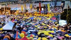 香港で2014年に起きた大規模デモ。参加者は、行動のシンボルとなった「雨傘」を一斉にさして抗議した=同年10月28日、鈴木玲子撮影