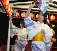 踊り船の上で、扇子を手に踊る中野美咲さん(手前)と杉山寿生さん