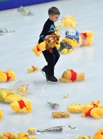 A junior skater picks up teddy bears that were thrown onto the rink, after Yuzuru Hanyu's short program of the Rostelecom Cup at Megasport Sport Palace in Moscow, on Oct. 20, 2017. (Mainichi)