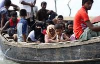 船に乗って避難する人たち。ミャンマー軍の目が届きにくい夜間に国境沿いを流れるナフ川を渡るケースが多く、対岸のバングラデシュに逃れた難民は早朝、歩いて難民キャンプへと向かっていく=コックスバザール近郊で2017年10月4日、宮武祐希撮影