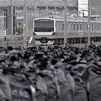 JR常磐線の富岡駅と竜田駅間の運行が再開され、富岡駅を出る上りの電車。手前は除染で出た廃棄物を入れた袋の仮置き場=福島県富岡町で2017年10月21日午前8時32分、西本勝撮影